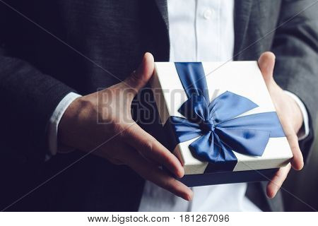 Horizontal close up of Caucasian man in black suit and white shirt offering a gift box with blue large ribbon selective focus natural light