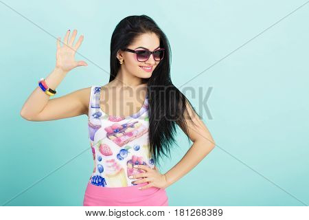 attractive young brunette woman in pink tank top on the blue background.  girl in sunglasses shows five fingers