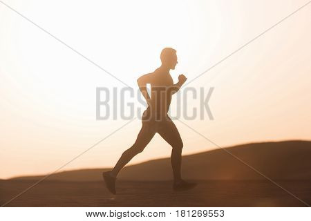 success and healthy lifestyle. man runner or fit male athlete running in desert sand dune at mountain in sun ray at sunset sunrise outdoor on white sky background. sprinting sport and marathon workout
