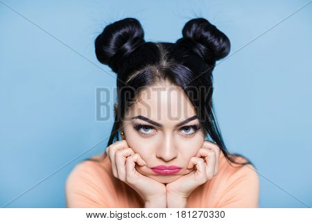portrait of sad and upset brunette woman with hair of mouse on the blue background