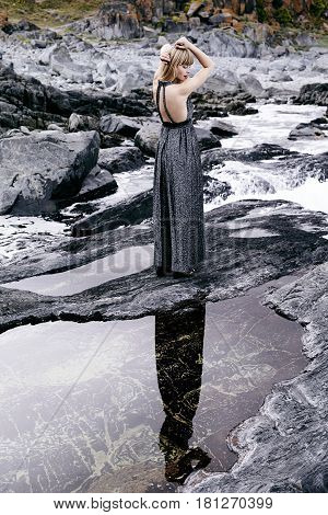 Sensuous woman in gray dress amidst rocks