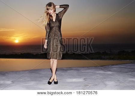 Glamorous fashion model standing at poolside at sunset