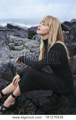 Bewitching blond woman sitting on rocks at beach