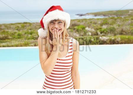 Swimsuit model in Santa hat giggling at poolside