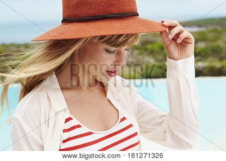 Cool young woman touching hat brim side view