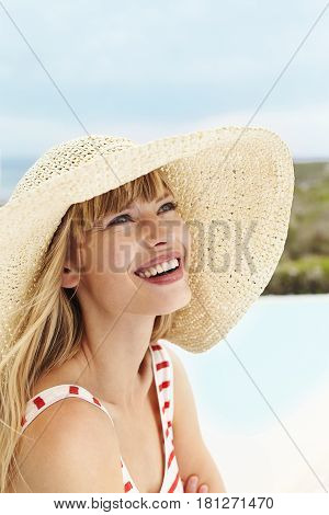 Beautiful young woman in sunhat looking away