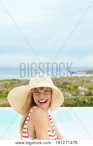 Laughing young model in sunhat at vacation