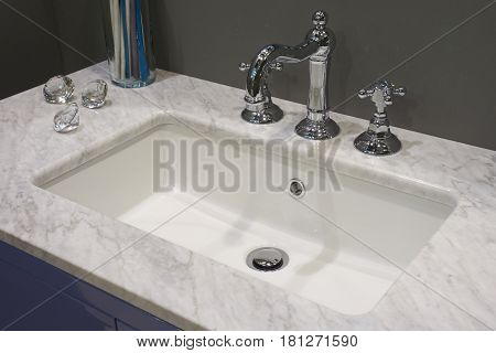 White inset ceramic washbasin with glossy metal mixer and marble table