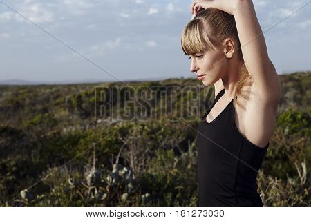 Young blond cool athlete stretching outdoors looking away