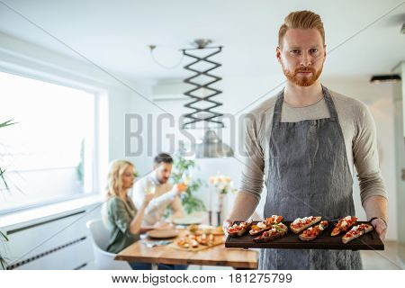 Shot of handsome young man serving delicious food for friends.