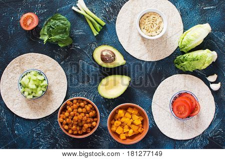 Ingredients for vegan tortillas: chickpeas butternut squash spring onion cucumber avocado on the dark blue table top view