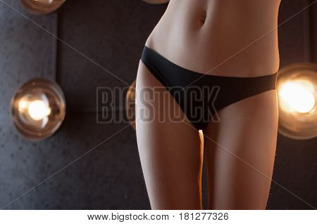 Suntanned beautiful harmonous well-groomed body of the young girl in a brassiere close up
