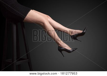 Long legs and high heel shoes on the dark background