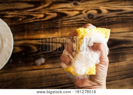 a sponge with soap bubbles in woman's hand