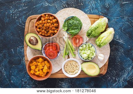 Ingredients for vegetarian tortillas on the wooden board chickpeas butternut squash spring onion cucumber avocado on the dark blue table top view copy space for text