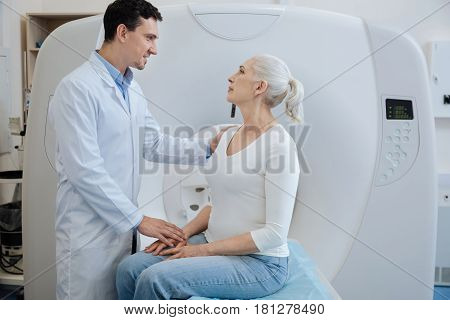 I have good news. Handsome joyful male oncologist looking at his patient and putting her hand on his shoulder while telling her good news