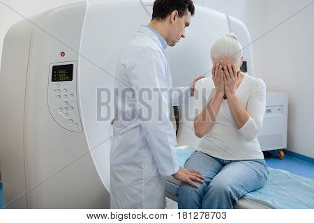 How much time do I have. Sad depressed elderly woman sitting on the examination table of CT scanner and covering her face while crying