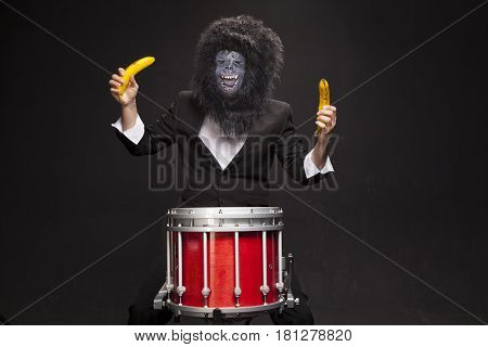 The man in the costume of a monkey. A guy with a marching drum and two bananas. A guy in a monkey costume with a drum