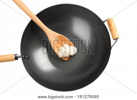 Spatula with coconut oil in wok on white background
