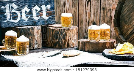 Mugs of beer, dried fish and potato chips on raw wood pub counter with natural stumps and oak barrel. Wood signboard with text 'Beer'
