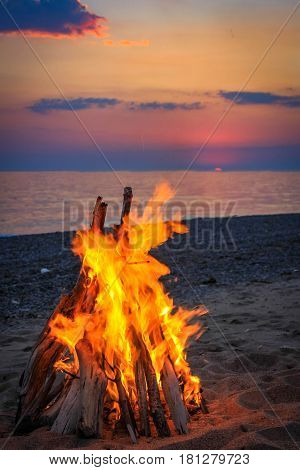 Bonfire on the beach by the sea at sunset