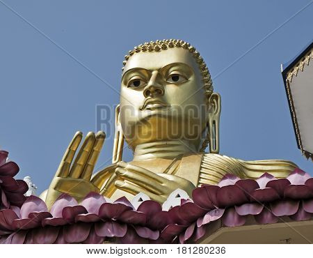 A giant gold statue of Buddha looks out over the entrance to the temple complex of Dambulla near Kandalarama in Sri Lanka.