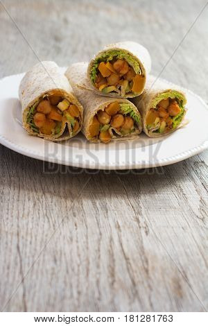 Vertical photo of four vegetarian tortillas with chickpeas butternut squash spring onion cucumber avocado on the dark wooden table copy space for text