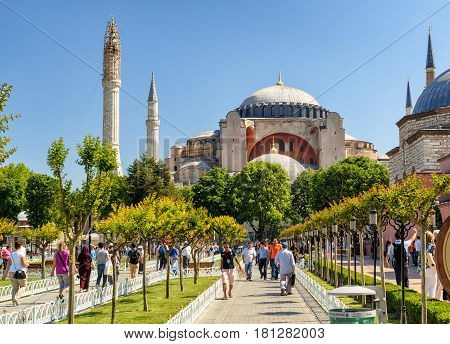 ISTANBUL - MAY 26, 2013: Tourists walk next to Hagia Sophia. Church of Hagia Sophia is the greatest monument of Byzantine Culture and tourist attraction.