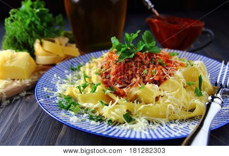 pasta Bolognese with fresh herbs on a blue dish