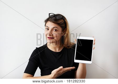 Smiling beautiful young woman european appereance wearing black dress and glasses holding her digital tablet showing and pointing to blank tablet pc monitor copyspace area for advertising text