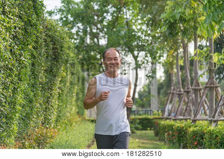 old man exercise by jogging at the park, health concept, senior man smile and run outdoor