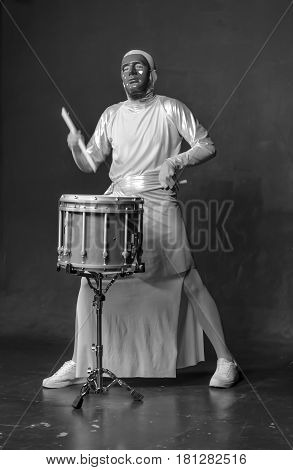 A guy in a suit with a marching drum. Black and white photo of the drummer. A man with a marching drum