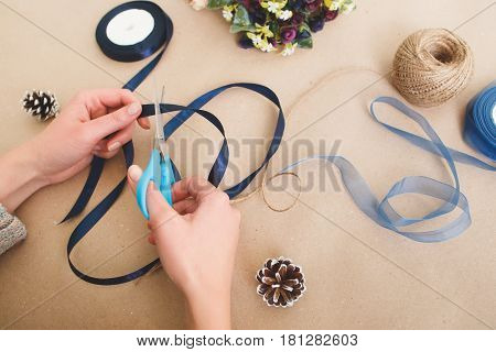 Unrecognizable woman make creative decorations from ribbons on beige background, top view. Hand with scissors cut blue satin strip. Craftsmanship, handmade creativity, hobby concept.