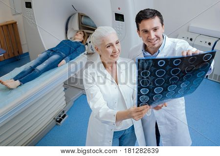 Doctors at work. Delighted handsome nice man standing with his colleague and examining a CT scan image while working together