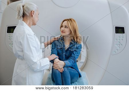 Pleasant friendly experienced doctor putting her hand on the patients shoulder and speaking while telling her the results of CT scanning