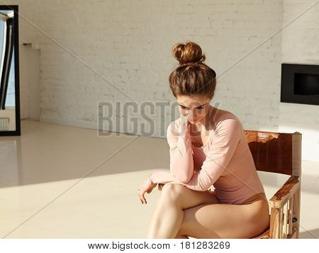 Handsome female student dressed in sexy bodysuit seating in the armchair looking down with shy and dreamy expression on her face. Young female ballet dancer resting between lessons in ballet school