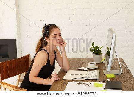 The talented young designer female thinks about design of new cafe working on freelance at home. Attractive Caucasian young woman with thoughtful emotion on a face looking pensive in the workplace