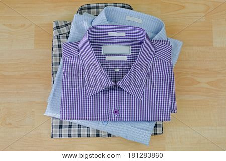 Stack of folded checked clothes, three 3 shirts after ironed ready to pack, on wooden background