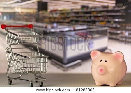 Pink piggy bank pig standing near mini shopping push cart with blurred supermarket background