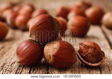 Full and peeled hazelnuts close-up. Macro photo of pile of filbert kernels, lot of nuts on blurred background. Bright autumn backdrop. Harvest, fall, food ingredient concept poster