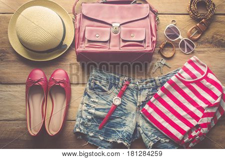 clothing and accesories for women placed on a wooden floor.