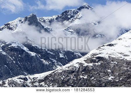Snowy mountain peaks surrounded by clouds in Glacier Bay national park (Alaska).