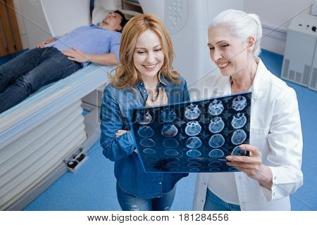No serious problems. Cheerful delighted positive woman standing near the oncologist and talking to her while looking at the X ray photo