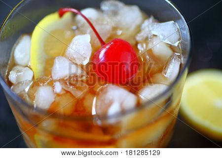 Whiskey sour cocktail with lemon crushed ice and a cherry