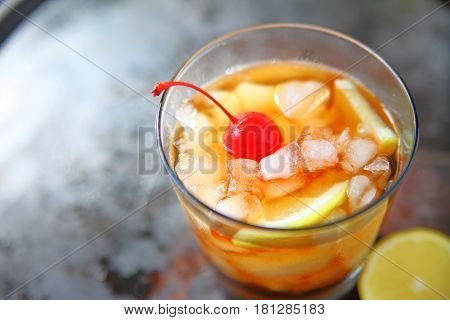 Overhead view of whiskey sour cocktail with lemon and cherry on crushed ice with room for text
