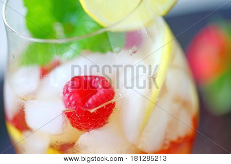 Closeup of cold drink with white wine lemon raspberries and mint