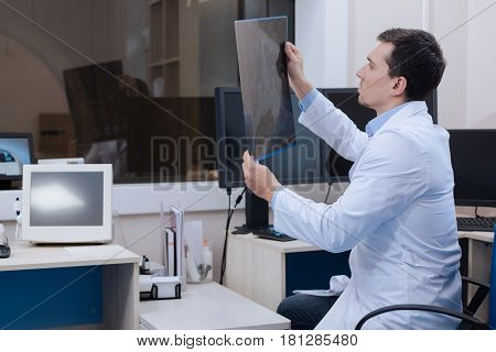 X ray scan. Nice handsome pleasant radiologist sitting in the chair and looking at the CT scan image while working in the CT lab
