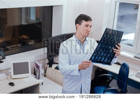 Its difficult to decide. Serious nice male radiologist holding an X ray scan picture and looking at it while thinking about possible diagnosis
