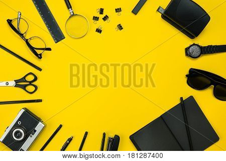 Black objects from the office on a yellow background. Work and creativity. Social media concept hero header image. Top view. Still life. Copy space