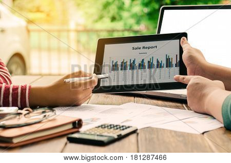 Business team analysis with financial graph in tablet at office workplace meeting